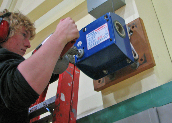Sitka senior Thor Becker tests out a special drill bit to raise the gym's basketball hoops. Photo by Robert Woolsey, KCAW - Sitka.