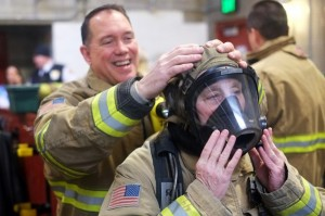 Firefighter Joe Mishler helps place on Juneau Assembly member Kate Troll's oxygen mask at Hagevig Fire Training Center. (Photo by Annie Bartholomew/KTOO)