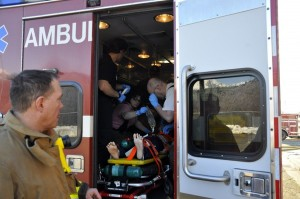 Participants load the dummy into the ambulance where they will perform CPR on the patient while the vehicle is in motion. (Photo by Annie Bartholomew/KTOO)