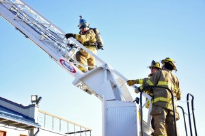 KTOO reporter Matt Miller climbs the ladder during the morning training at Hagevig Fire Training Center. (Photo by Annie Bartholomew/KTOO)