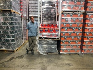 Alaskan Brewing Co. co-founder Geoff Larson stands next to cans of Amber Ale stacked in the Juneau-based brewery's warehouse. (Photo by Casey Kelly, KTOO - Juneau)