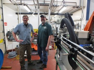 Alaskan Brewing Co. co-founder Geoff Larson (left) and Plant Manager Curtis Holmes stand next to the brewery's new canning line. (Photo by Casey Kelly, KTOO - Juneau)