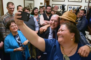 "Rep. Jonathan Kreiss-Tompins (center) celebrates by posing for a ""selfie"" with supporters of House Bill 216, his legislation making 20 Alaska Native languages official state languages alongside English. The bill had passed the Senate only moments earlier at 3 a.m., April 21, 2014. (Photo by Skip Gray/Gavel Alaska)"