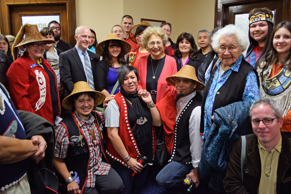 Rep. Jonathan Kreiss-Tomkins (in suit coat and blue shirt) and supporters of House Bill 216 gather in a Capitol hallway for a group photo to celebrate passage of the bill through the House State Affairs Committee. The bill would symbolically make 20 Alaska Native languages official state languages alongside English. (Photo by Skip Gray/Gavel Alaska)
