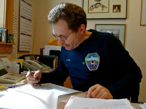 Dave Berg looks over a spread sheet of this year's visitors at Viking Travel, Inc. (Photo by Angela Denning, KFSK - Petersburg)