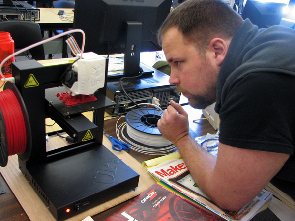 Metlakatla Science teacher Jason Pipkin watches as the printer creates metric screws for a quadcopter his students are building. (KCAW photo/Robert Woolsey)
