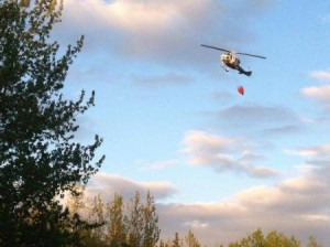 A helicopter drops water on the fire near Soldotna Monday night (Ariel Van Cleave photo)