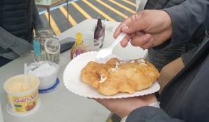 Darrin Austin puts butter and powdered sugar on his fry bread. (Photo by Jeremy Hsieh/KTOO)