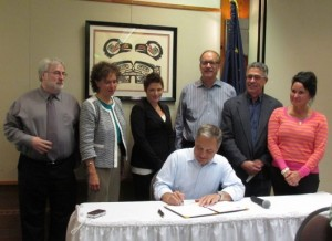 Gov. Sean Parnell signs SB99 into law during a special Ketchikan Chamber of Commerce lunch on Monday. (KRBD photo)