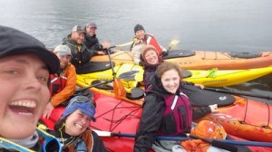 Clockwise from left: Sarah Outen and her kayaking partner Justine Curgenven, with Unalaskans Jeff Hancock, Josh Good, Keils Kitchen, Pipa Escalante, Melissa Good and Annie Ropeik in kayaks on Unalaska Bay. /Courtesy: Sarah Outen via Twitter
