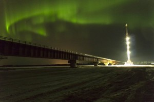 Floodlights on a crane illuminate the far end of the bridge-construction site in Salcha as aurora dance overhead. (Credit Alaska Railroad)