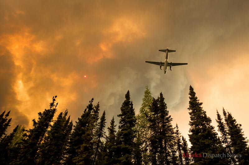 An airplane prepares to drop retardant on a fire burning on the edge of Browns Lake in the Funny River neighborhood of Soldotna on Saturday afternoon, May 24, 2014. The Funny River fire burned over 100,000 acres on Alaska's Kenai Peninsula.
