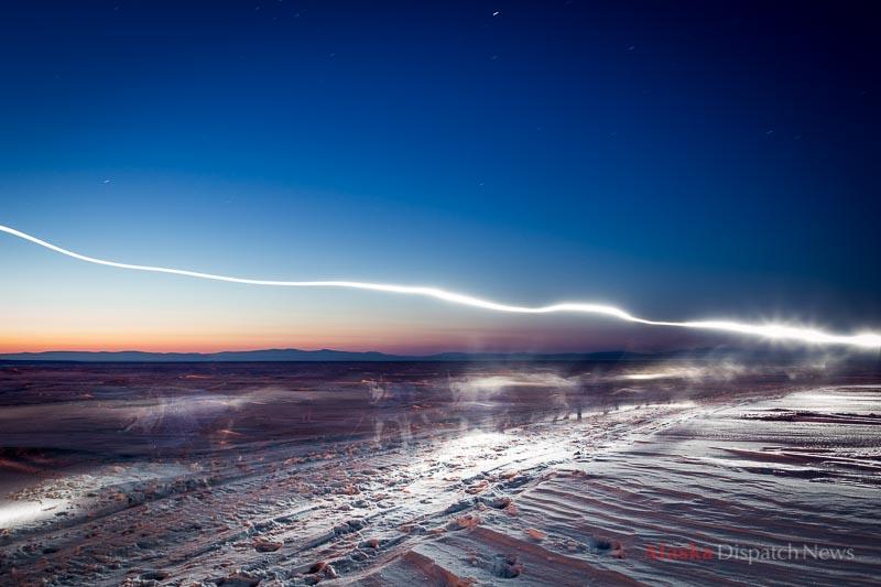 Iditarod winner Mitch Seavey's headlamp creates a streak of light as he crosses the sea ice before dawn near Koyuk during the 2013 Iditarod Trail Sled Dog Race on March 11, 2013.