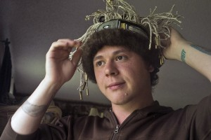 Ricky Tagaban models one of his headbands in his living room.  (Photo by Annie Bartholomew, KTOO - Juneau)