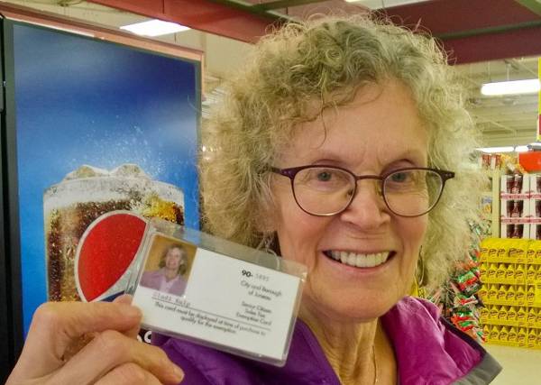 Gladi Kulp shows her senior tax exemption card at IGA. She says she normally doesn't use it for small purchases, but her cashier knows her and prompted her for the card number. She saved about 85 cents this trip. (Photo by Jeremy Hsieh/KTOO)