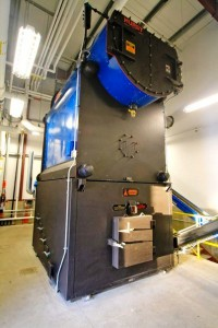 This biomass-fueled boiler at Tok School burns chipped timber waste to generate heat and electricity for the campus. (Credit KUAC file photo)