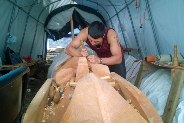 Haida carver T.J. Young carves fine details into an Eagle totem pole in progress. (Photo by Jeremy Hsieh/KTOO)