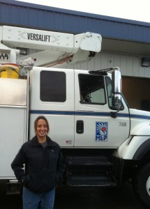 Lineman Deborah Kelly stands in front of an ML&P truck.