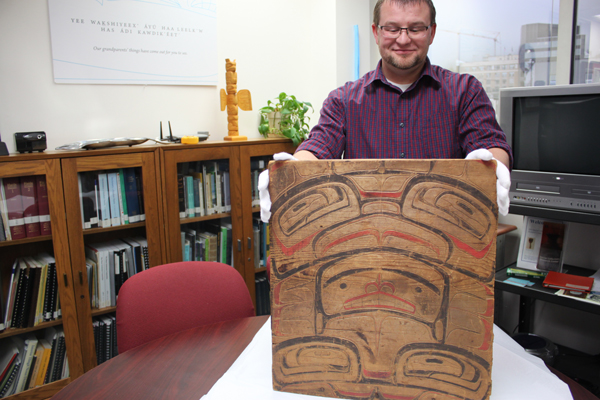 Archivist and collection manager for Sealaska Heritage Institute Zachary Jones holds up the wood panel, which arrived last week. (Photo by Lisa Phu/KTOO)
