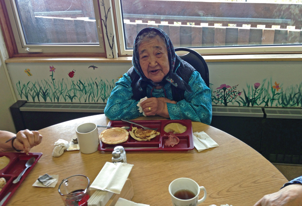 Elder Lucy Jacob enjoys lunch with her friends in the cafeteria at the Senior Center. (Photo by Charles/KYUK)