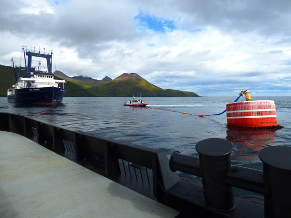 The Sea Trader (left), seen from the deck of the tug James Dunlap, waits to be tied on to Unalaska's emergency mooring buoy. At center, the city's harbor patrol boat stands by to assist. (Annie Ropeik/KUCB)