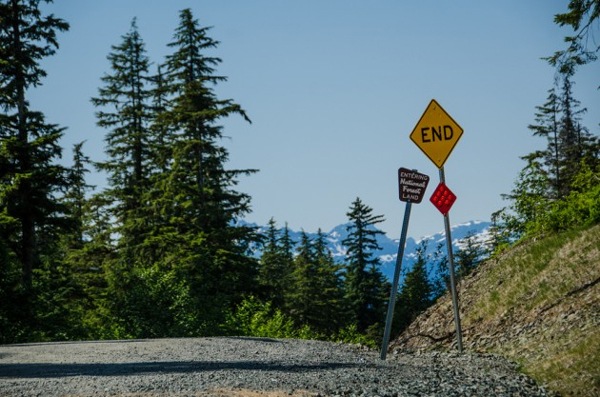 Signs mark the end of Juneau's Glacier Highway in 2013. The latest environmental impact statement maintains a preference to extend the road 47 miles north along the east side of Lynn Canal to a new ferry terminal. (Photo by Heather Bryant/KTOO)