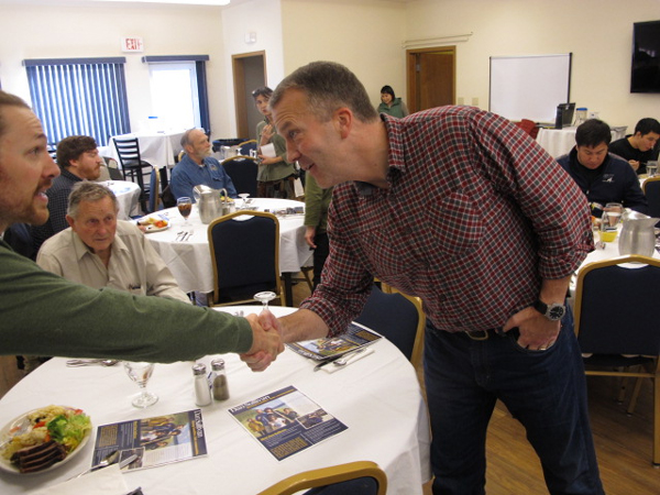 Sullivan greets Leif Albertson at the Bethel Chamber of Commerce lunch. (Photo by Ben Matheson / KYUK)