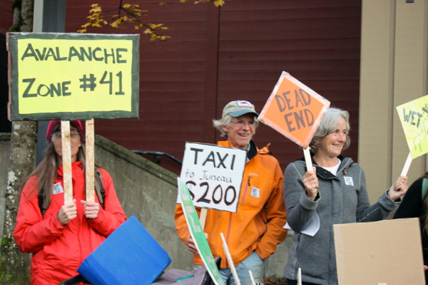 A few dozen people participated in a rally the Southeast Alaska Conservation Council organized outside Centennial Hall. They were supporting ferries and opposing an extension of the Juneau's main road. (Photo by Jennifer Canfield/KTOO)