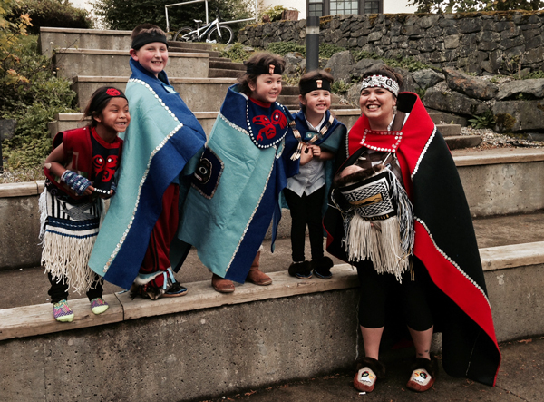 "Heather Powell, Education Director at the Sitka Native Education Program, poses with some young dancers after the Naa Kahídi Dancers' 20th anniversary performance at the Sheet'ká Ḵwáan Naa Kahídi. ""We are giving them an opportunity to have a sense of pride, a sense of community,"" said Powell."