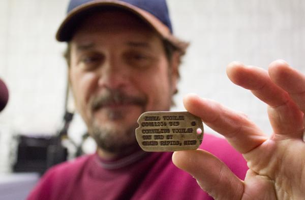Mario Gandolfo displays Earl Vogelar's dog tag. (Photo: Jenn Ruckel, KNOM)