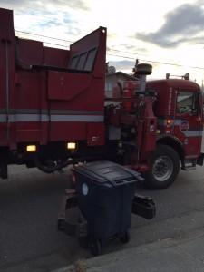 A recycle truck grasps onto a bin in Anchorage. Hillman/KSKA
