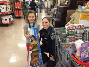 Lilly shops with Officer Bonnie Charles for Christmas presents for herself and her family. Hillman/KSKA