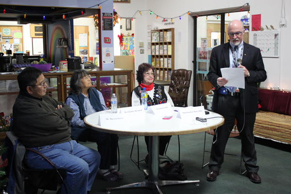 Juneau Schools Superintendent Mark Miller reads his decision in the company of three guests – Marcelo Quinto, Charlotte McConnell and Katherine Hope – who attended Native boarding schools as children. (Photo by Lisa Phu/KTOO)