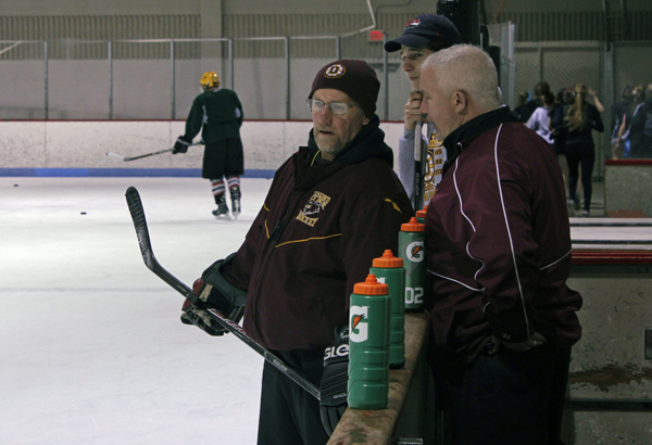 Dennis Sorenson confers with another coach at Dimond High School's hockey practice. (Photo by Josh Edge, APRN - Anchorage)