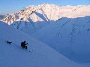 Happy memory: Michael Hopper slices through powder on a telemark turn down a slope in the Eastern Alaska Range near Black Rapids with his canine companion Rowdy back in 2010. (Credit Mike Hopper)