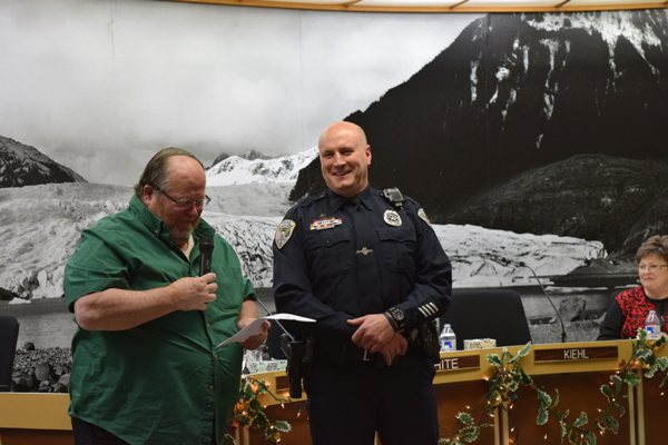 Mayor Merrill Sanford reads a speech recognizing JPD Officer Blaine Hatch for his recent award as Alaska Municipal League Employee of the Year. (Photo by Casey Kelly/KTOO)