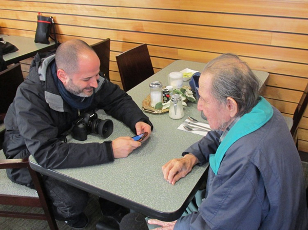 Photographer Danny Goldfield shows centenarian Henry Neligan some apps on his smartphone while talking at the Ketchikan Indian Community cafeteria.
