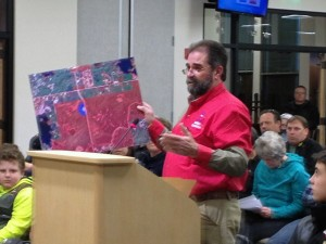 Neil Moss, president of Alaska Scholastic Clay Target Program,  holds up a map of land the ASCTP wants for a shooting range at the Matanuska-Susitna Borough Assembly meeting on Tuesday. (Photo by Ellen Lockyer, KSKA - Anchorage)