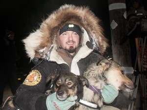 Pete Kaiser at the 2015 Kuskokwim 300 finish with his lead dogs, Palmer and Rosie. – Photo by Chris Pike