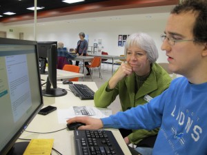 Micah Williams gets help from Navigator Joan Fisher at the Loussac Library. Photo Credit: Annie Feidt