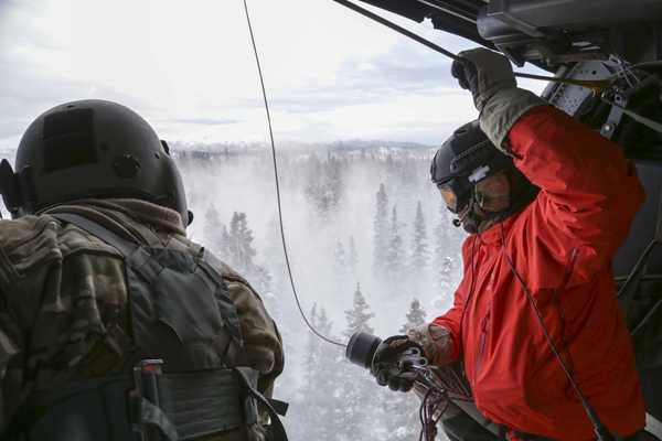 Alaska Air Guardsman Capt. Johh Romspert, a 212th Rescue Squadron combat rescue officer, prepares to be lowered via hoist out of an HH-60 Pave Hawk Helicopter during a training mission held near Mount Susitna Dec. 16. (U.S. Army National Guard photo by Sgt. Balinda O'Neal)