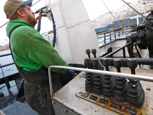 Ron Mitchell drops nets onto the deck of the F/V Seadawn during pollock season. (Lauren Rosenthal/KUCB)