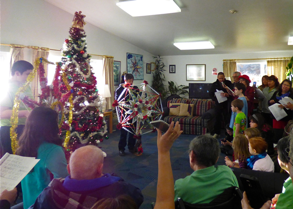 The congregation and other Unalaskans gather for a starring at Unalaska's senior center. At far right, Father Evon Bereskin joins in the caroling.  (Photo by Annie Ropeik, KUCB - Unalaska)