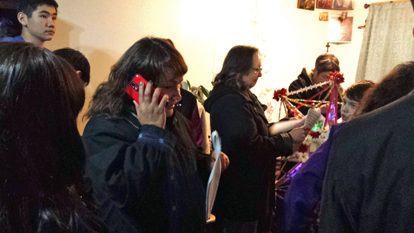 Marie Schliebe, left, calls a friend to let them listen in on a home starring. At right, Sharon Svarny Livingston looks over her packet of Russian carol lyrics. (Photo by Annie Ropeik, KUCB - Unalaska)