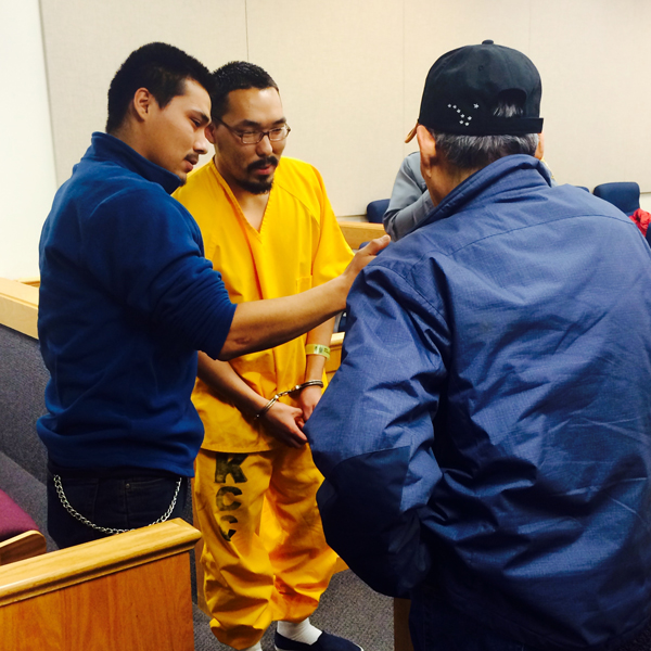 Colten Zaukar (center) visits with his brother and father after his sentencing Friday. (KYUK photo)