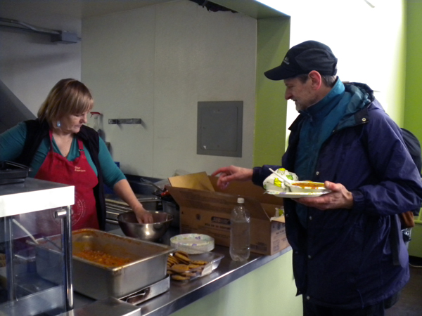 Glory Hole staffer Mindy Lee serves the first meal at the shelter's headquarters since the building shut down for repairs two months ago. (Photo by Kevin Reagan/KTOO)