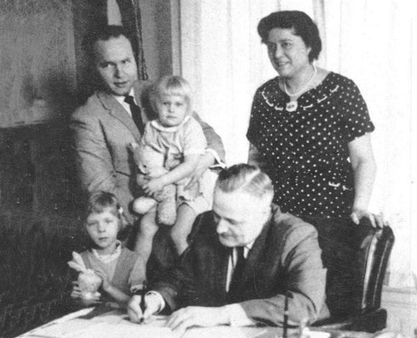 Joyce Kerttula stands behind Gov. Bill Egan as he signs a bill by Rep. Jay Kerttula, holding his daughter Anna. Beth Kerttula is standing beside the governor. (Uncredited photo via Alaska House Democrats)