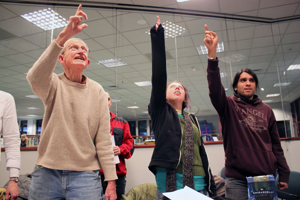 Participants of the Tlingit Language Learners Group point to the ceiling during an exercise called Total Physical Response. (Photo by Lisa Phu/KTOO)