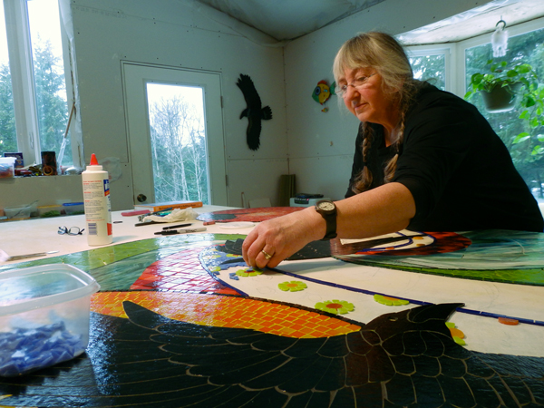 "Sharon Svenson works on the ""Taking Flight"" mosaic."