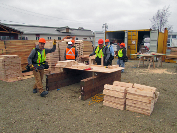 AVCP Crews prepare to put the integrated truss building that will be new dormitories for their flight and aircraft maintenance schools. (Photo by Ben Matheson/KYUK)